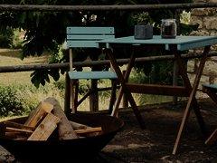 Außenbereich ein Tisch mit Stühlen davor eine Feuerschale