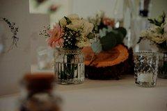 Tischdekor aus einem Blumenstrauß, einer Holzscheibe und Teelichtern