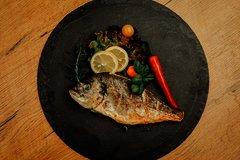 Fisch angerichtet auf Platte mit Zitrone und Chili
