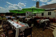 Schöne weitläufige Terasse mit aufgespannten Sonnenschirmen über den gedeckten Tischen