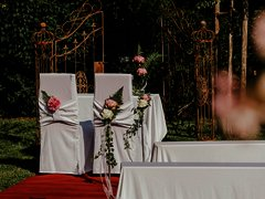 Romantisch dekorierte Trauszenerie im Außenbereich mit Sitzmöglichkeit